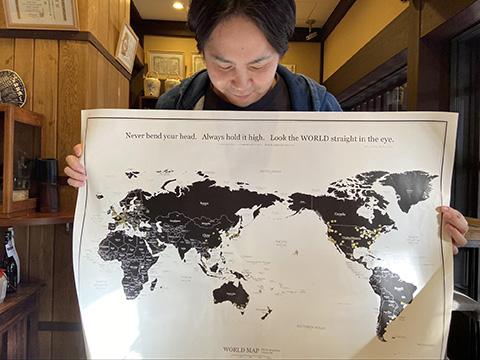 世界地図上に、来訪客の居住地が金色の丸シールでマークされている