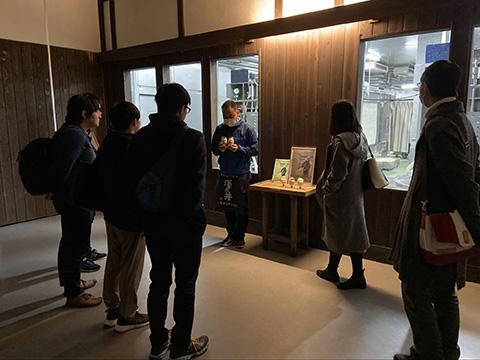 精米前後の米サンプルと窓向こうの搾り機を見ながら、米ぬかと酒粕の活用について学ぶ